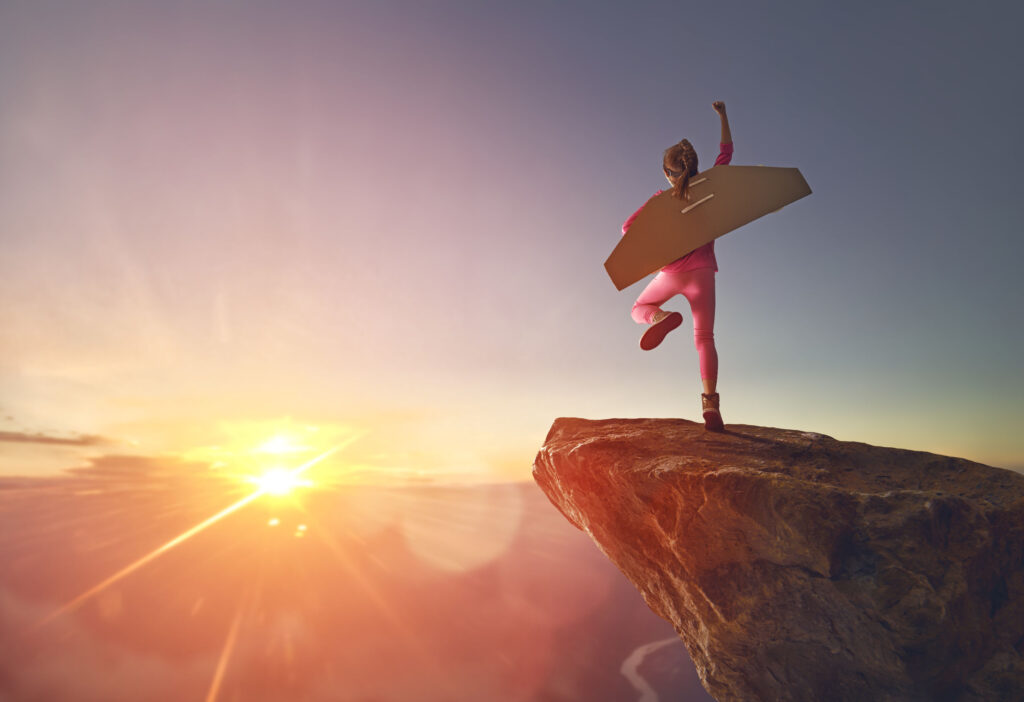 Girl with airplane wings jumping off cliff