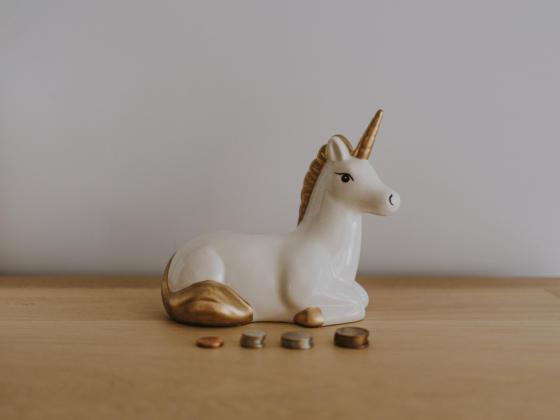 Unicorn coin bank with money in front of it
